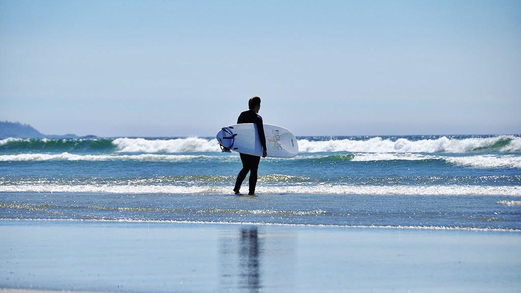 Un surfeur qui hésite à se jeter à l'eau vers Tofino - Île de Vancouver